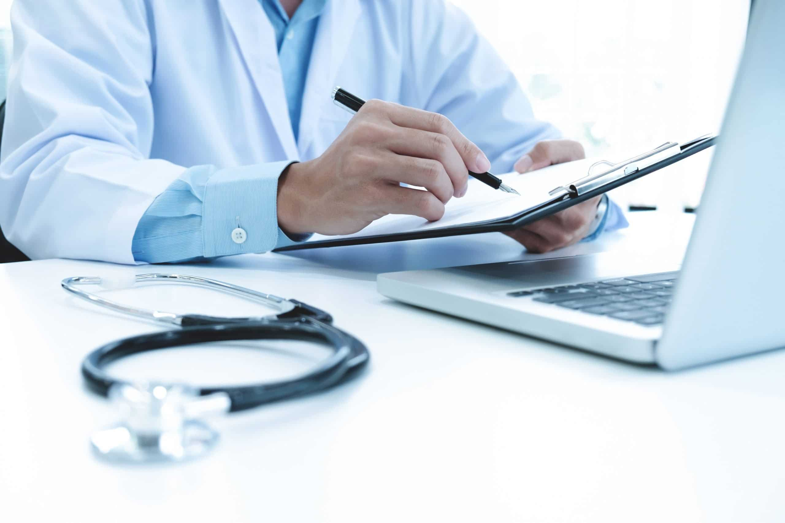 Doctor working with laptop computer and writing on paperwork